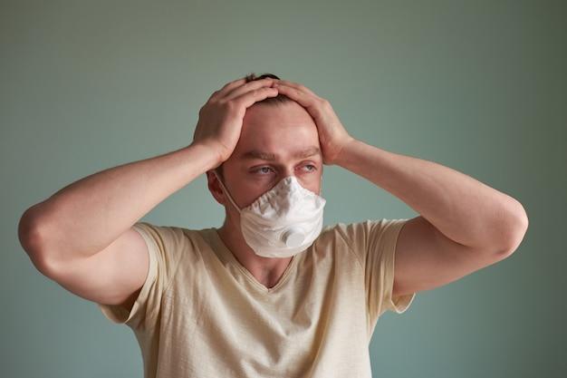 医療マスクで病気の白人のヨーロッパ人、発熱に苦しんで、両手で頭を抱えています。