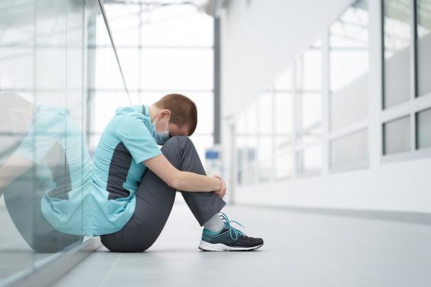 バーンアウトの概念。目を閉じて動揺のように見えるクリニックの廊下の床に座って疲れた白人女性の短い髪の医者