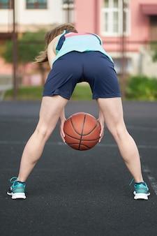 屋外コートでストリートバスケットボールをして赤毛の白人少女