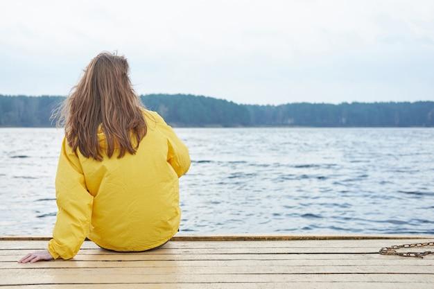 湖の桟橋に座っていると遠くを見て黄色のレインコートの赤毛の女性。