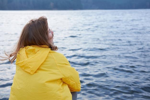 座っている黄色のレインコートの赤毛の女性