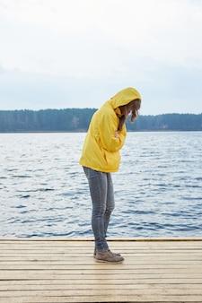 湖の桟橋の上に立って、暖かくしようとして自分を抱いて黄色いレインコートを着た赤毛の女性。曇った厄介な秋の天気。