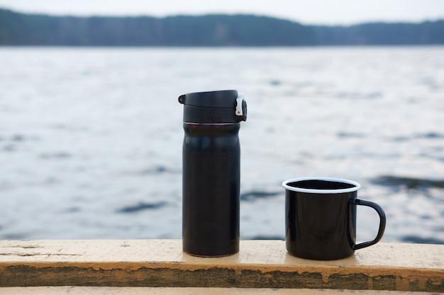 魔法瓶、湖の上のコーヒーの黒いマグカップ、