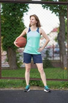 赤毛の女の子が屋外のバスケットボールコートの上に立ってボールを押しながら笑みを浮かべて