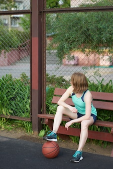 座っていると屋外のバスケットボールコートでゲームを待っている地面にボールを持つ赤毛の細い白人少女
