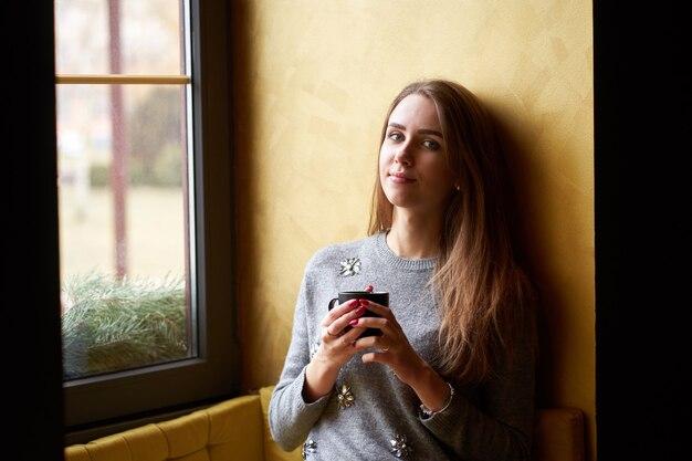 カフェでコーヒーやお茶を飲んだ長い髪の若いきれいな女の子。