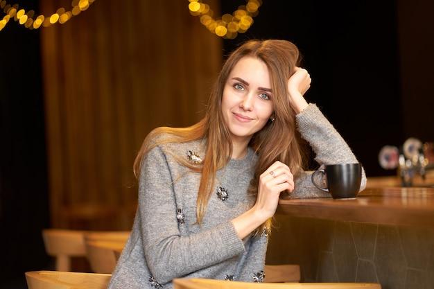 長い髪とフレンドリーな笑顔がカフェに立地し、コーヒーを飲みながら魅力的な魅力的な女性の肖像画。