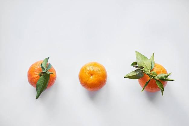 Рождественские фрукты. три оранжевые свежие мандарины или мандарины с зелеными листьями лежат на белом фоне. вид сверху.