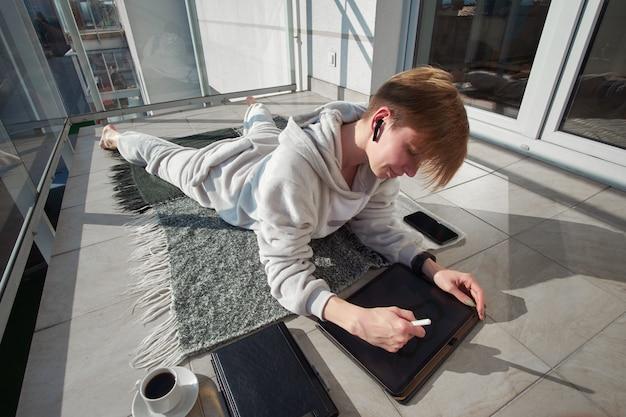 Короткошерстная рыжая девушка-иллюстратор цифрового искусства, одетая в пижаму, лежит на солнечном балконе, слушает музыку в наушниках, пьет кофе и работает на планшете