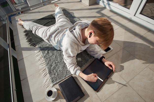 Короткошерстная рыжая девушка-иллюстратор цифрового искусства, одетая в пижаму, лежит на солнечном балконе и работает на планшете