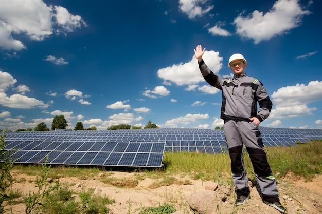 ソーラーパネルエンジニアまたは白いヘルメット、保護用の黄色いメガネ、灰色の服を着た電気技師がソーラーパネルフィールドの近くに立って、こんにちはジェスチャーをしています。