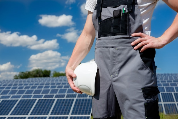 ソーラーパネルエンジニアまたは労働者が白い保護用のヘルメットを保持
