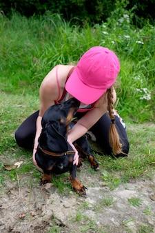 犬、友情の概念で遊んでピンクの帽子の少女