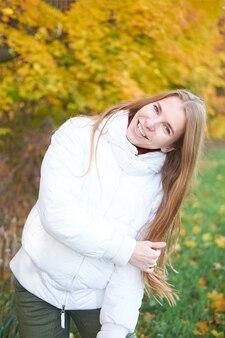 白いジャケットと緑のズボンを着て美しい自然な長い髪を持つ魅力的な陽気な少女の肖像画。背景に黄色の秋の木々。秋の時間。