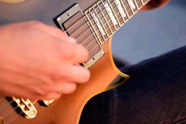 Руки гитариста играют на электрогитаре