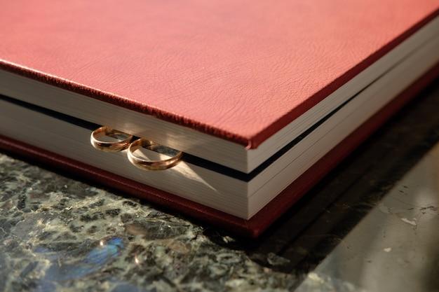 Коричневый кожаный обтянутый свадебный альбом с парой обручальных золотых колец, торцом.