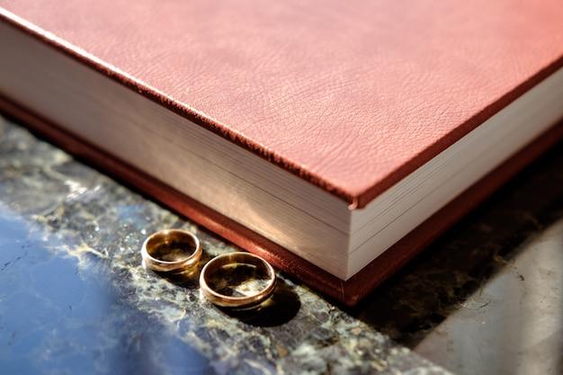 Коричневый кожаный альбом с парой обручальных золотых колец