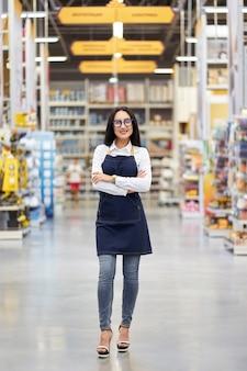 ショッピングセンターの背景に若い魅力的な肯定的な女の子売り手