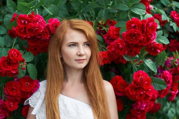 Портрет довольно рыжая девушка, одетая в платье белого света на фоне цветущих роз.