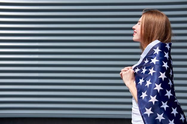 アメリカの星条旗の旗。赤い塗られた唇と目を閉じて米国旗で立っていると太陽を楽しんで幸せな美しい赤毛の女の子。灰色の金属パネルの背景。コピースペース。