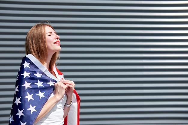 アメリカの星条旗の旗。赤い塗られた唇と目を閉じてアメリカの国旗のそばに立って日光浴を楽しんでいる生姜美人を笑っています。灰色の金属パネルの背景。