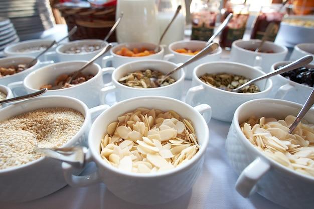 オープンビュッフェでナッツ、ドライフルーツ、蜂蜜、オート麦の朝食に健康的なスナックがたくさん