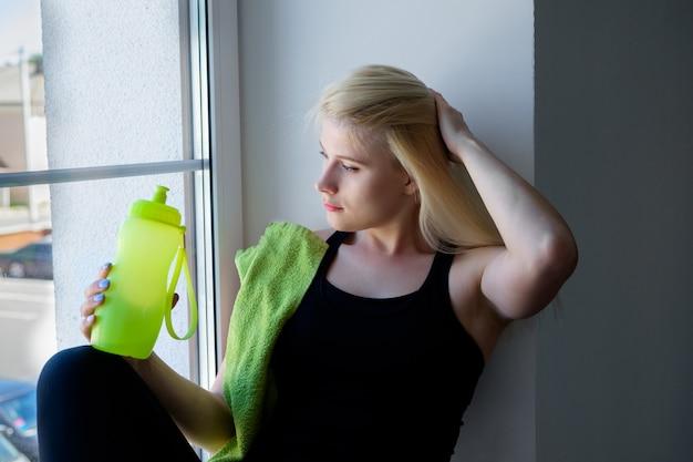 Молодая женщина пьет воду в тренажерном зале