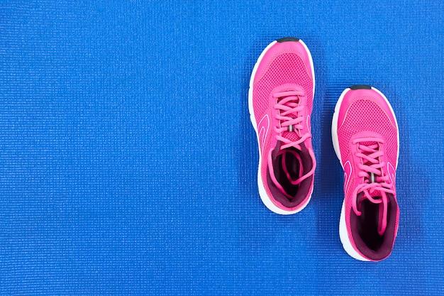 青色の背景に女性のためのピンクのランニングスニーカーのペア。上面図