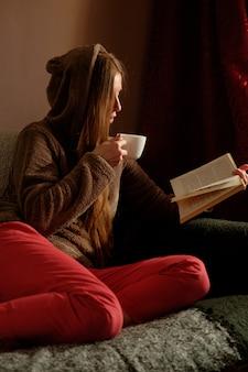 本を読んで面白いパーカーで赤毛生姜の女の子、コーヒーを飲みながら、ソファーに横になっていると笑顔