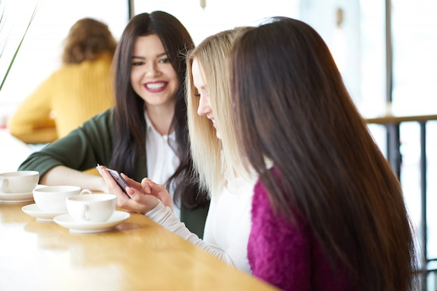 Улыбающиеся подруги смотрят фотографии на смартфоне, сидят в кафе и пьют чай