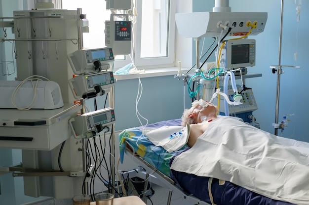 Интубированный взрослый белый человек под авл лежит в коме в отделении интенсивной терапии. пациент в критическом состоянии.
