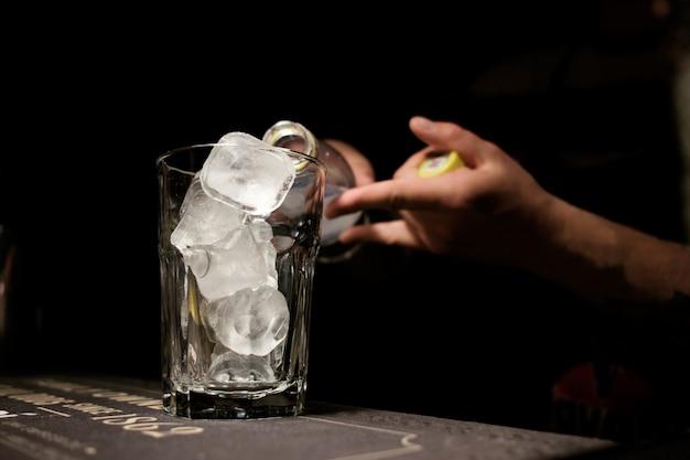 バーテンダーがカクテルを作り、氷で満たされたグラスに強壮剤を注ぐ