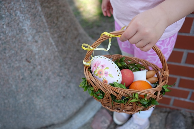 イースターバスケットの卵を保持している女の子。