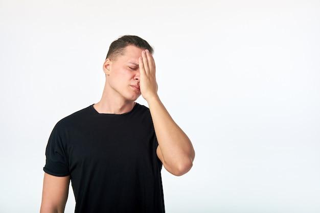 目を閉じて頭に触れて魅力的な若い男。頭痛に苦しんでいる人。