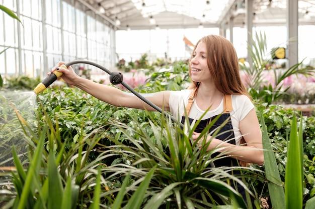植物市場の温室植物を注ぐと笑顔で赤毛の若い女性労働者