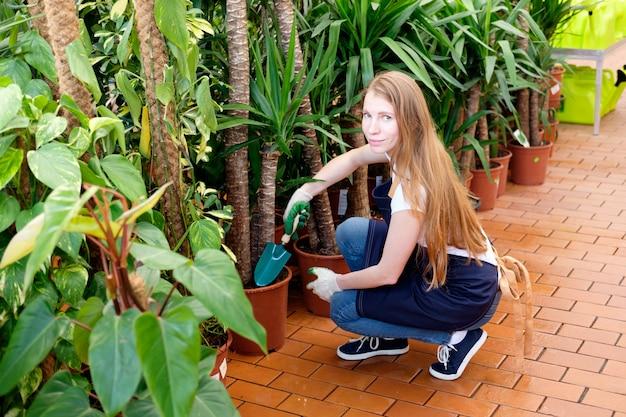 花の世話をする植物市場の温室で赤毛の若い女性労働者
