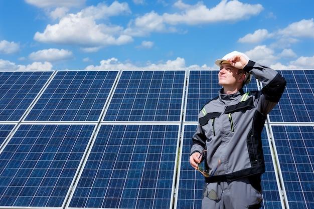 Работник инженера солнечных батарей в белой бочке