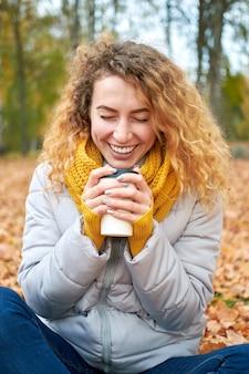 秋の紅葉の上に座って、リラックスして秋の公園の眺めを楽しむ女の子