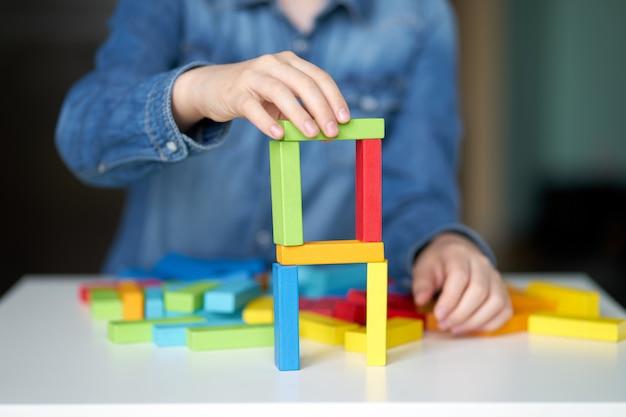 Настольная игра. ребенок играет с разноцветными деревянными кубиками.