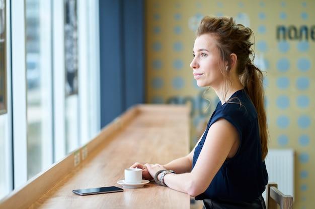 Рыжая белая девушка в синей блузке пьет кофе в кафе и смотрит в окно