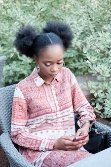 Черная афро девушка в этническом платье и наушниках на шее сидит в летнем кафе, смотрит что-то в смартфоне