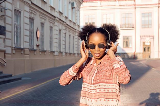 Черная афроамериканская девушка гуляет по вечернему городу и слушает музыку в наушниках. девушка в солнечных очках в улыбках лета и смотреть на заходе солнца.
