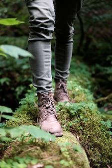 旅行中の女性の足は、森の苔むした丸太をブーツで履きます。旅行の概念。