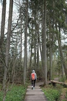 Молодой активный путешественник с оранжевым рюкзаком гуляет по мосту в заповеднике.