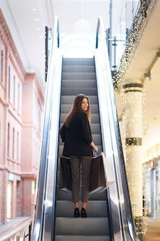 Рождественская распродажа. черная пятница. портрет довольно улыбается женщина в модной одежде с большими сумками на сером фоне металла