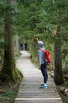 Туризм. путешественник маленькой девочки с оранжевым рюкзаком идя на деревянный мост в заповеднике и снимая видео с камерой действия.