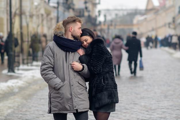 若い幸せなカップルが冬の降雪の下で町の通りを歩いて、笑顔でお互いを抱きしめ、男は寺院で彼女のガールフレンドにキス、女の子の応答に笑顔