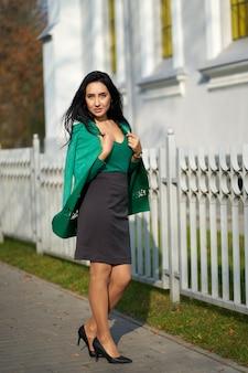 灰色のスカートと緑のジャケットを保持している緑のセーターを着ている若い魅力的なブルネットの少女