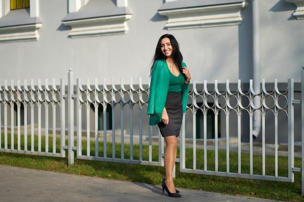 Красивая улыбающаяся брюнетка в серой юбке, зеленом свитере и стильной зеленой куртке позирует перед камерой