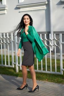 Молодая привлекательная брюнетка девушка в серой юбке и зеленом свитере держит зеленую куртку